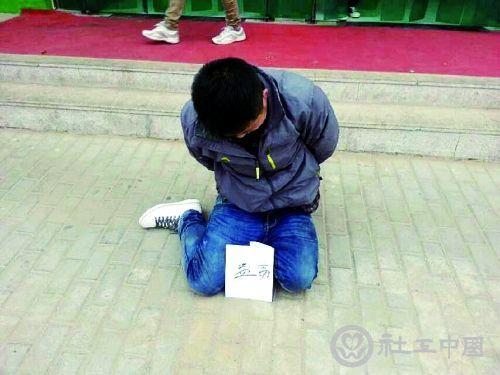 小偷被抓后,双手背在身后,跪坐在学校的餐厅门口