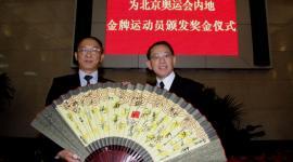 杨受成博士获国家体育总局局长刘鹏(左)赠送一把齐集所有金牌运动员签名的纸扇。