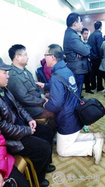 """安置区内,面对痛哭的家属,一名志愿者双膝跪下安慰,连说""""要坚持,要坚持"""" 摄/法制晚报记者 洪煜 刘汩 易朵 柴程"""