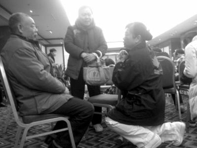 慈济基金会志愿者(右)在安抚马航失联飞机乘客家属。_b