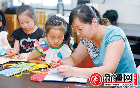 7月10日,在乌鲁木齐幸福城市花园社区,社工金艳红在教小朋友用废旧台历做笔记本。