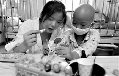 社工正在与一位孩子做游戏,医务社工为患者和患者家属提供心理疏导等服务。_b