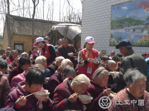 红会志愿者管理岗位社工崔艳玲在为老人们午餐