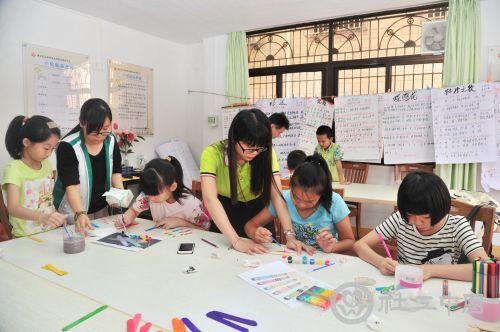 社工教孩子们在收集的雪糕棒上涂上颜色,制成精美的装饰品