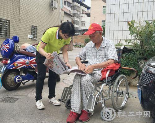 社工为社区老人读报纸